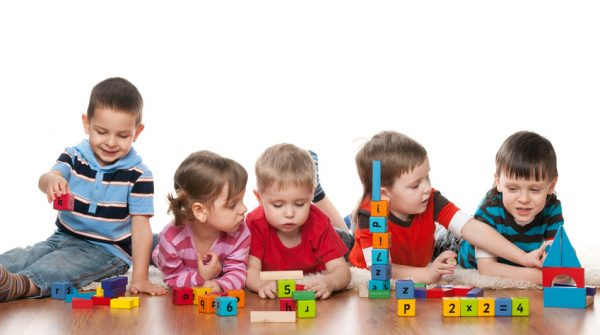 Five clever children are playing on the floor in the kindergarten