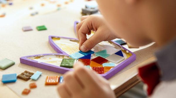 The mosaic puzzle art for kids, children's creative game. The hands are playing mosaic at table. Colorful multi-colored details close up. Creativity, children's development and learning concept